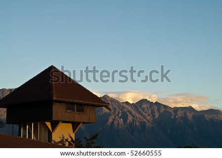 Wooden house on rooftop with Mountain in the background - stock photo