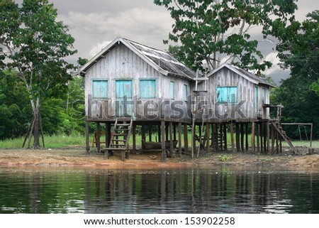 Wooden house on the river bank, Amazon River, rainy season, Brazil. - stock photo