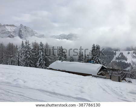 Wooden house standing by the ski slopes in Italian Alps on a cloudy day. - stock photo