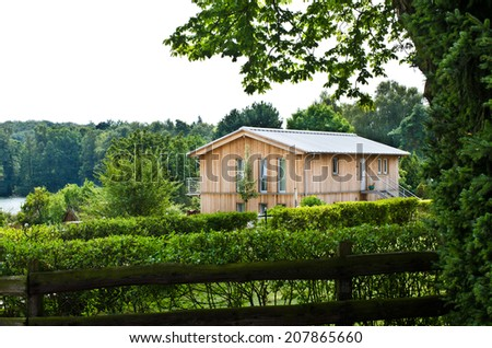 wooden house with big green park - stock photo