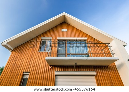 Wooden house with meadow in front of it - stock photo