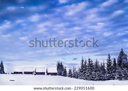 Wooden houses in winter snowy forest - stock photo