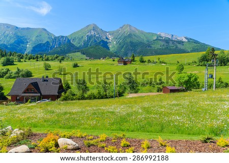 Wooden houses on green meadow with Tatry Bielskie Mountains in background in summer, Slovakia - stock photo