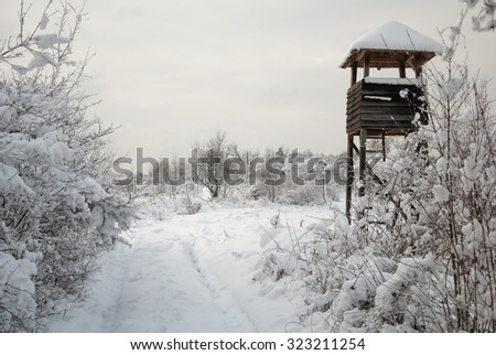 Wooden hunting tower in forest in winter snowy time. - stock photo