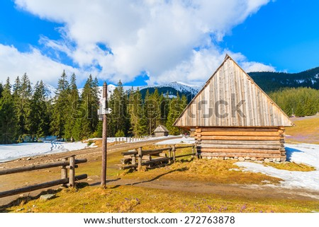 Wooden hut and mountain trail sign in Chocholowska valley in spring season, Tatra Mountains, Poland - stock photo