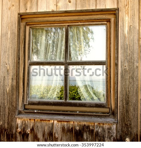 wooden hut (23) and the window is mirroring the green nature, mountains, trees and a lake - stock photo