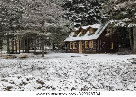 wooden hut under snow - stock photo