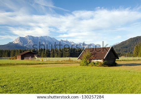wooden huts on alpine meadows in morning sunlight, Germany - stock photo