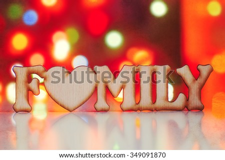 Wooden inscription Family with garland lights on background in vintage style.