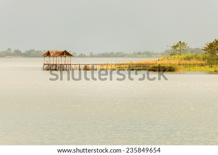 Wooden jetty  and stilt hut on lake Poso in central Sulawesi, Indonesia. Low contrast, soft light, optimal for backgrounds. - stock photo