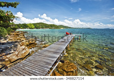 Wooden jetty in tropical beach, textured stones of the coastline is at foreground, and eastern coastline of Ko Samet island is at background, Thailand - stock photo