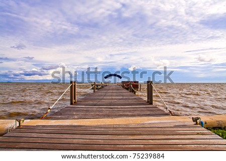 Wooden jetty into the sea with blue sky wide - stock photo