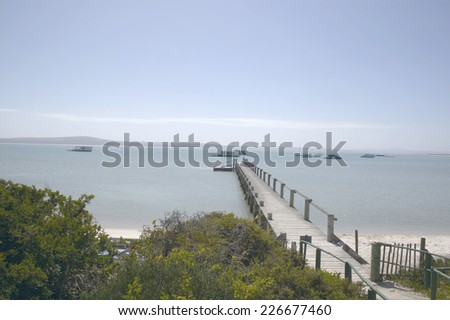 Wooden jetty leading out to sea - stock photo