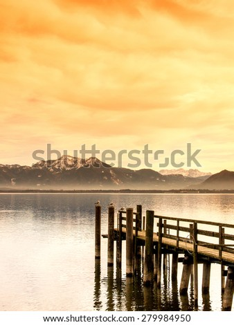 wooden jetty on lake chiemsee with alps in background - stock photo