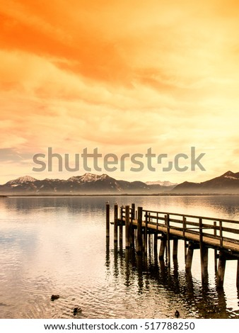 wooden jetty on lake chiemsee with alps in background