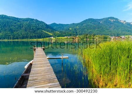 Wooden jetty on shore of Weissensee alpine lake in summer landscape, Austria - stock photo