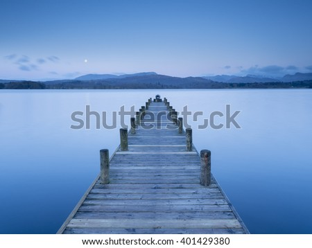 Wooden jetty on the calm waters of Windermere as the moon rises over the Coniston fells.