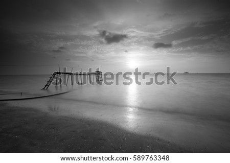 Wooden jetty on the muddy beach during sunset