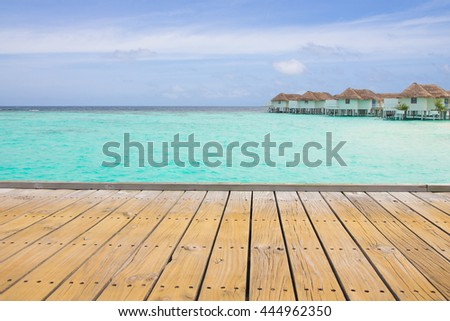 Wooden jetty over the beautiful Maldivian sea with Water bungalows - stock photo