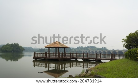 Wooden jetty with reflection in morning mist - stock photo