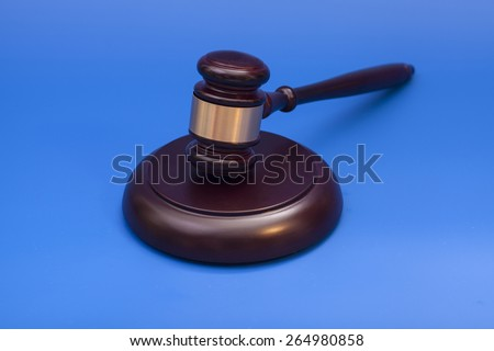 Wooden judge gavel and soundboard isolated on blue background - stock photo