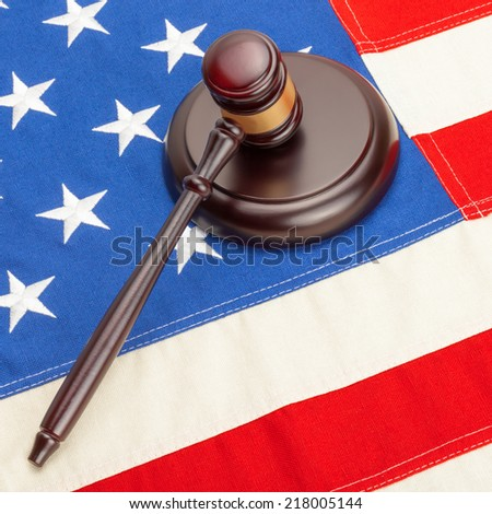 Wooden judge gavel and soundboard laying over US flag - 1 to 1 ratio - stock photo