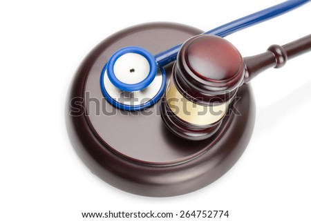 Wooden judge gavel and stethoscope on white - stock photo