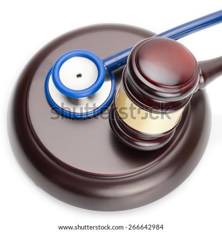 Wooden judge gavel and stethoscope on white - close up shot - stock photo