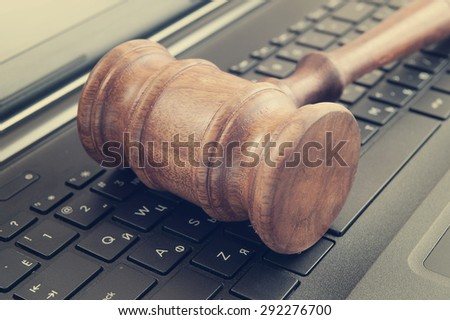 Wooden judge gavel on a laptop computer, cyber law or crime concept - stock photo