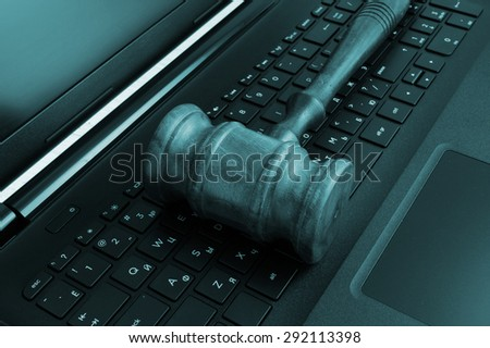 Wooden judge's gavel on a laptop computer, cyber law or crime concept
