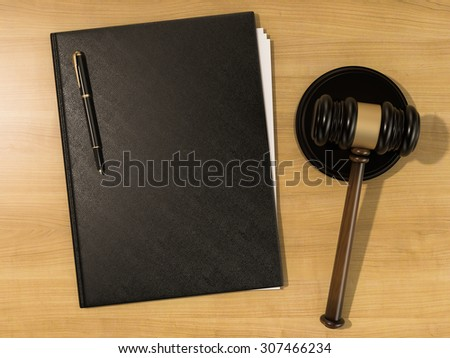 Wooden judges gavel and leather folder on the wooden background. High resolution - stock photo