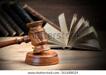 Wooden Judges Gavel And Open Old Law Books On The Rough Wooden Table In The Background. Law Concept. Front View, Close Up - stock photo