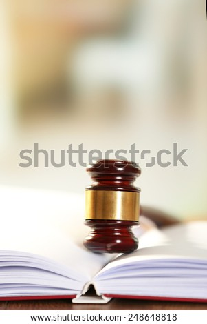 Wooden judges gavel lying on law book, close up - stock photo