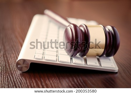 Wooden judges gavel on a computer keyboard, receding view with focus to the head with its brass decoration conceptual of online law enforcement and auctions
