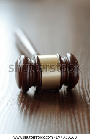 Wooden judges gavel with a central brass band around it lying with the handle facing away on a wooden desk or table with shallow dof conceptual of law enforcement and judgements in court - stock photo
