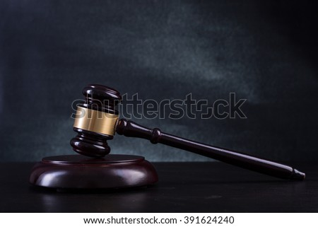 Wooden Judges gavel with black background. - stock photo
