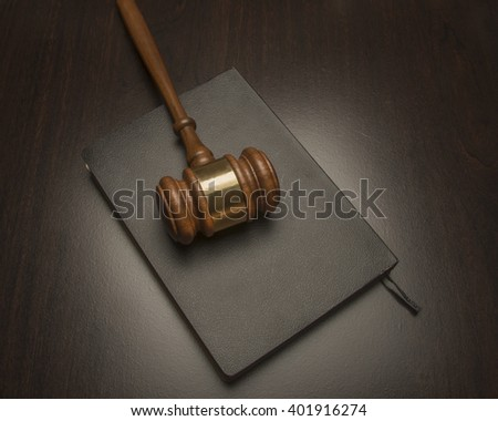 Wooden judicial gavel/Judicial Gavel/ Wooden judicial gavel is on top of a black book