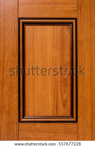 Wooden kitchen cabinet door made from maple. Traditional style with red cherry color,  Isolated close up.