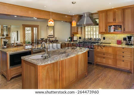 Wooden kitchen interior with appliances and kitchen island.  - stock photo