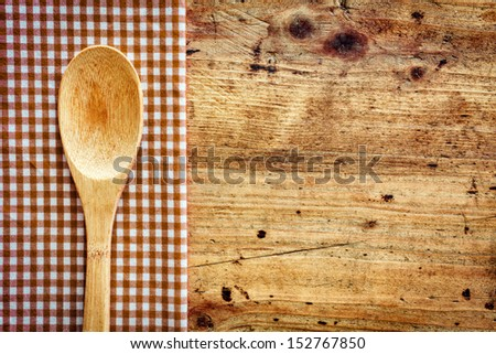 Wooden kitchen spoon on a fresh checkered rustic red and white napkin on a wooden counter with copyspace - stock photo