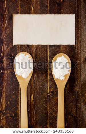 Wooden kitchen spoon with flour and starch. - stock photo