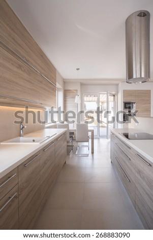 Wooden kitchen unit in bright luxury interior - stock photo