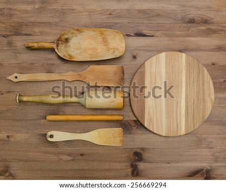 Wooden kitchen utensils  and cutting board on old  wooden table - stock photo