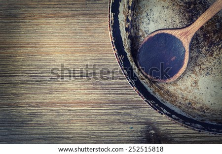Wooden kitchen utensils on the table. Recipe book wooden spoon old pan in a retro style on wooden table  - stock photo