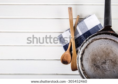 Wooden kitchen utensils on the table. Wooden spoon old pan in a retro style on wooden table. Free space for your information and products. - stock photo