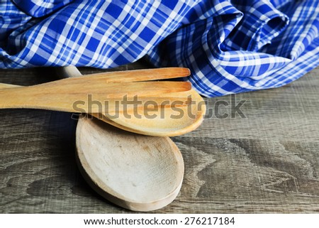 Wooden Kitchen Utensils on wooden background. Spoon,  fork and towel - stock photo