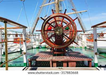 Wooden lacquer steering wheel of the sailboat. - stock photo
