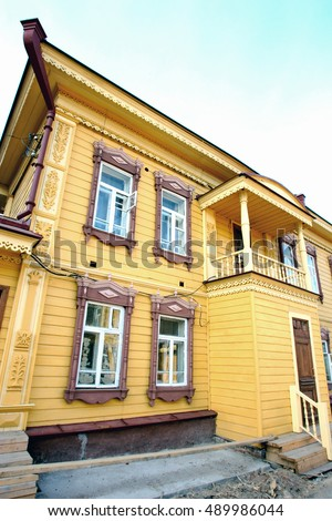 "Wooden lacy architecture of old wooden houses in Tomsk in Siberia. The restored house, building. On the Russian on the building: ""street name and house number"""