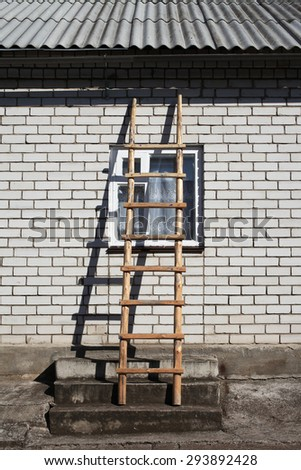 Wooden ladder on brick wall over window under slate roof