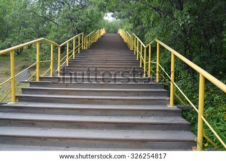 Wooden ladder with a yellow handrail in park. Bottom view